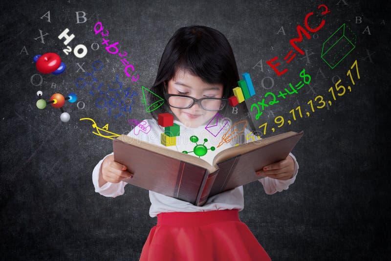 Libro di lettura adorabile della ragazza con la formula fotografie stock libere da diritti