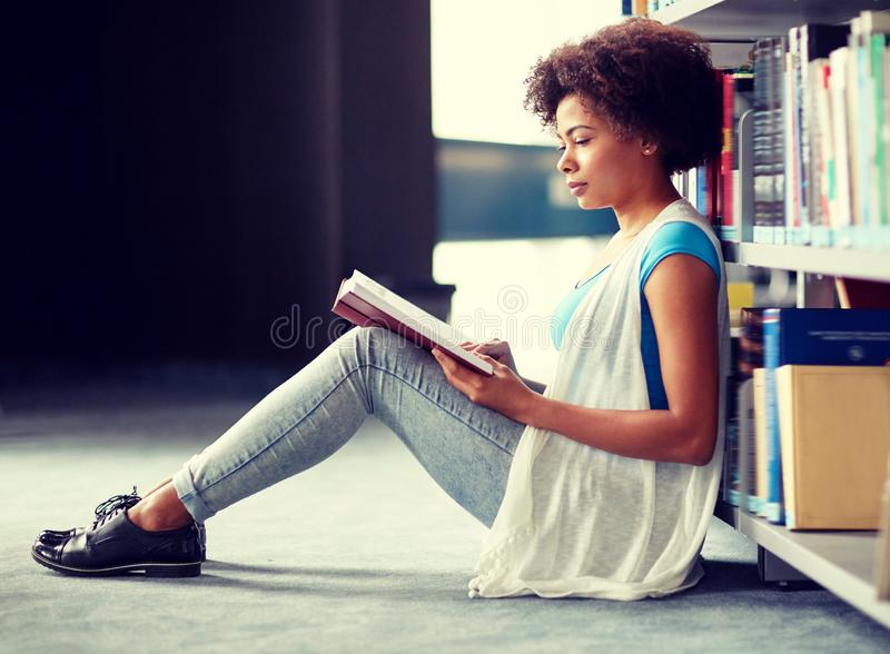 Libro di lettura africano della ragazza dello studente alla biblioteca immagini stock