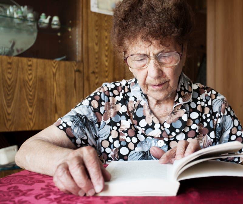 Libro di lettura anziano della donna immagine stock libera da diritti