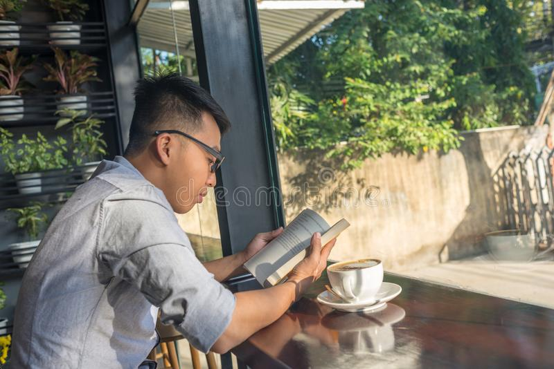 Libro di lettura asiatico dell'uomo di mattina immagine stock libera da diritti