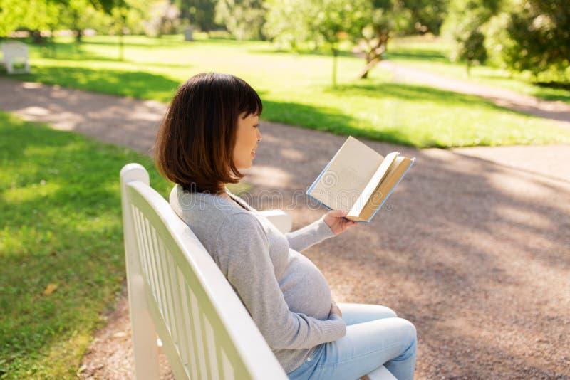 Libro di lettura asiatico incinto felice della donna al parco fotografia stock