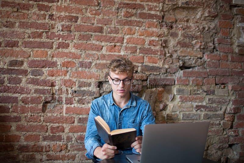 Libro di lettura astuto dello studente di college dell'uomo, seduta con il computer portatile nello spazio dilavoro fotografie stock libere da diritti