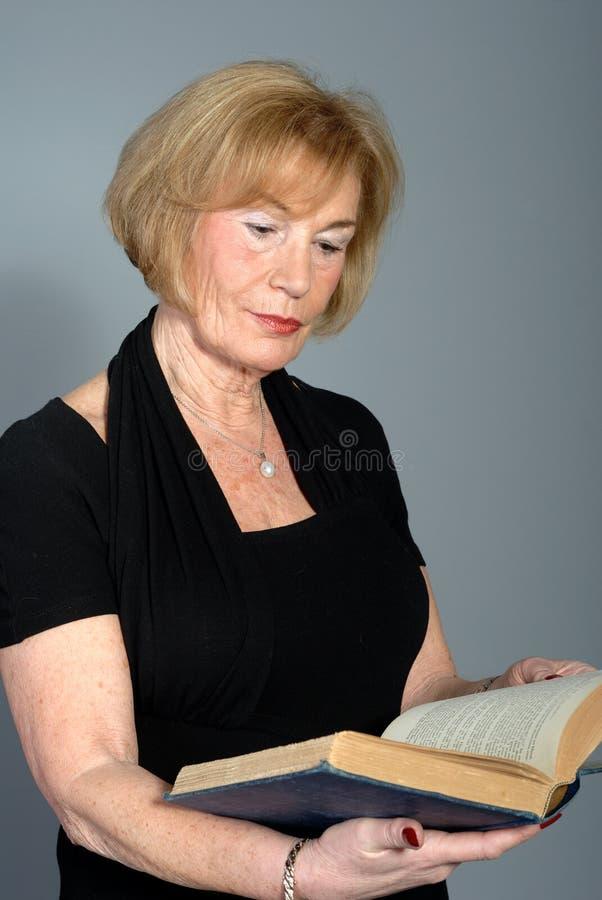 Libro di lettura attraente della donna più anziana fotografia stock libera da diritti
