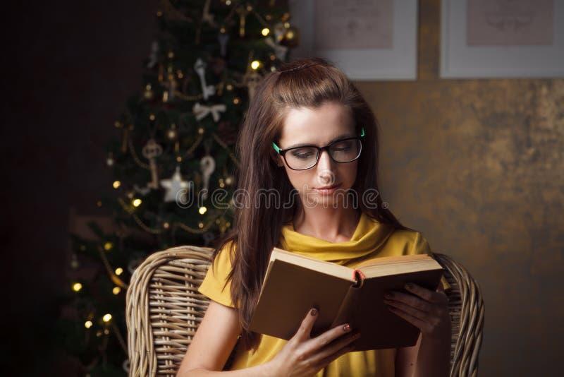 Libro di lettura attraente della giovane donna vicino all'albero di Natale fotografia stock libera da diritti