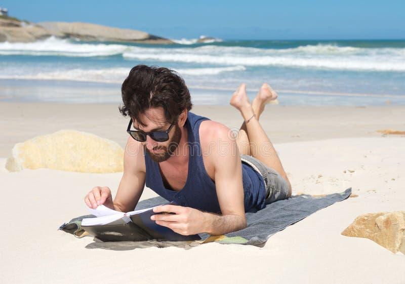 Libro di lettura bello del giovane alla spiaggia immagine stock libera da diritti