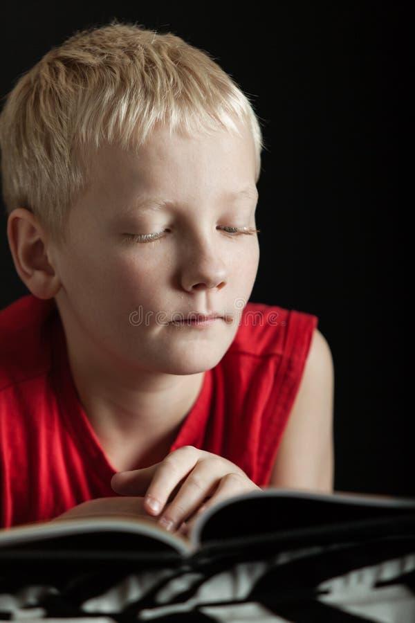 Libro di lettura biondo sveglio del ragazzo immagini stock