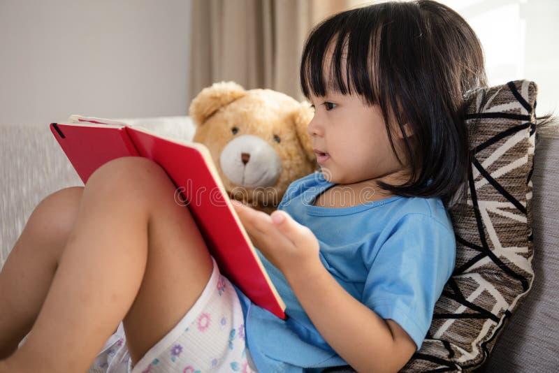 Libro di lettura cinese asiatico della bambina con l'orsacchiotto fotografie stock