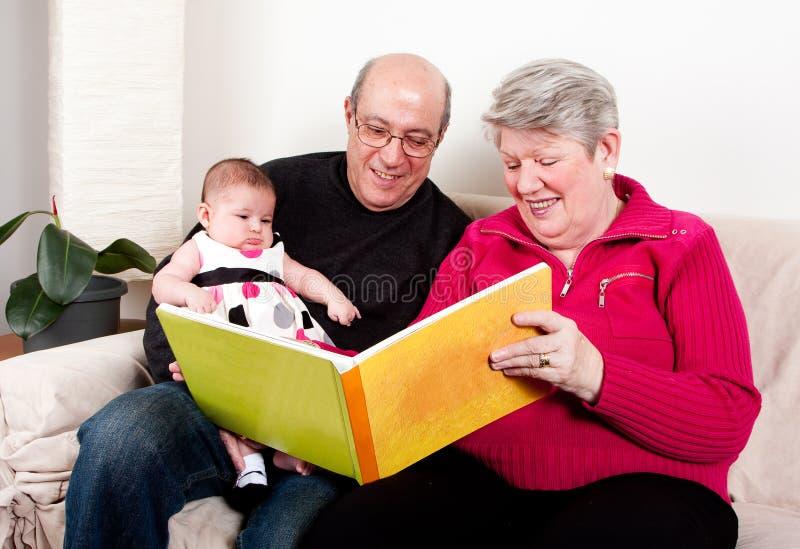Libro di lettura dei nonni alla neonata fotografia stock libera da diritti