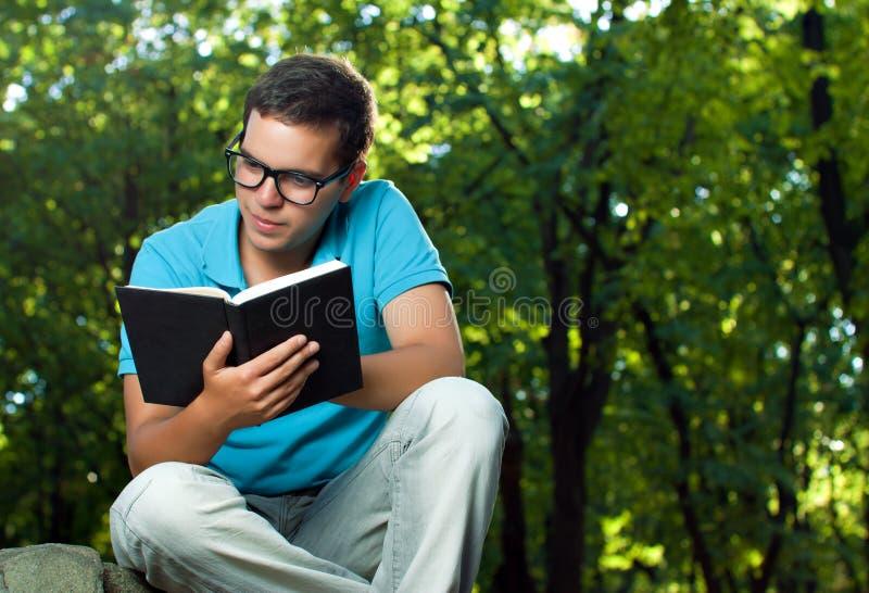 Libro di lettura del giovane fotografie stock