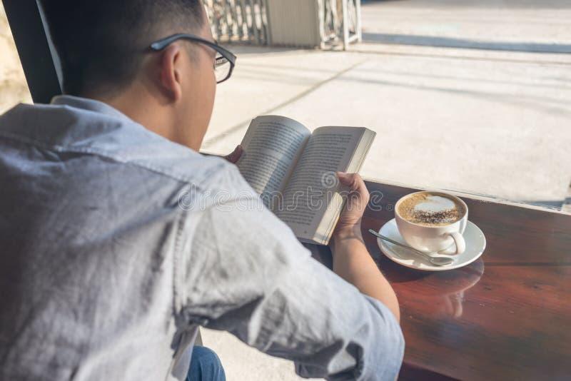 Libro di lettura del giovane e caffè bevente immagine stock