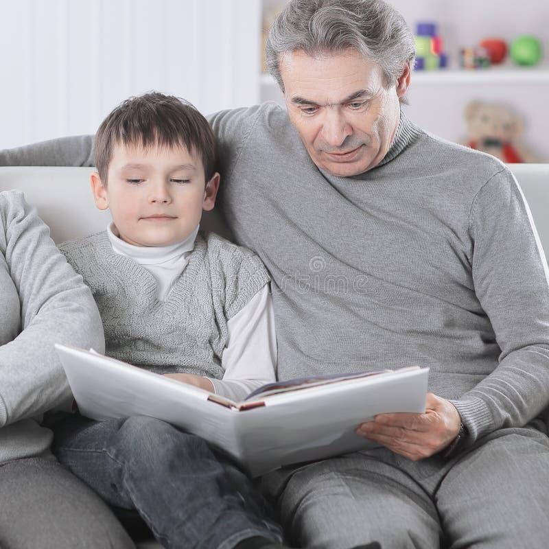 Libro di lettura del nonno e della nonna al suo nipote Il concetto di istruzione fotografia stock libera da diritti