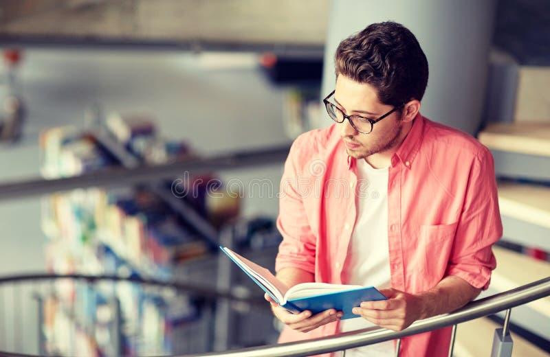 Libro di lettura del ragazzo dello studente o del giovane alla biblioteca immagini stock