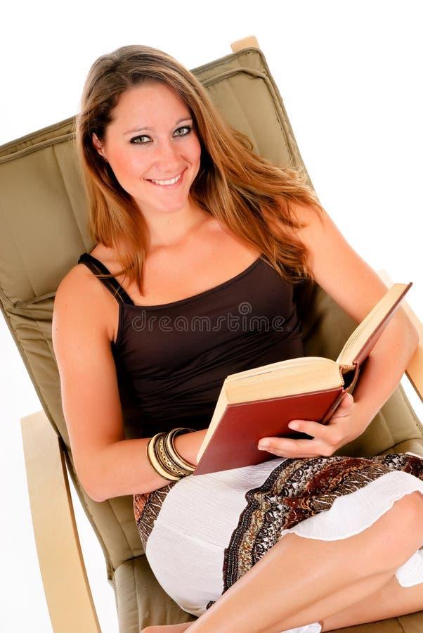 Libro di lettura del sofà della donna immagini stock