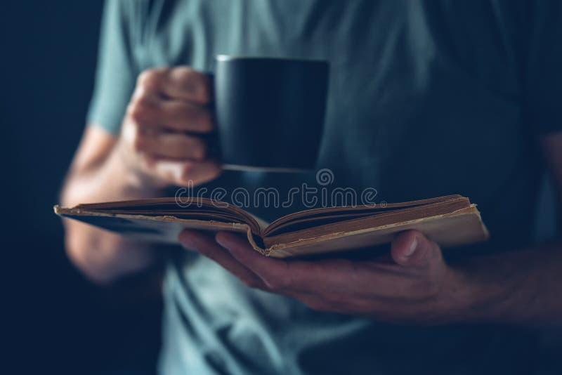 Libro di lettura dell'uomo e caffè bevente fotografia stock