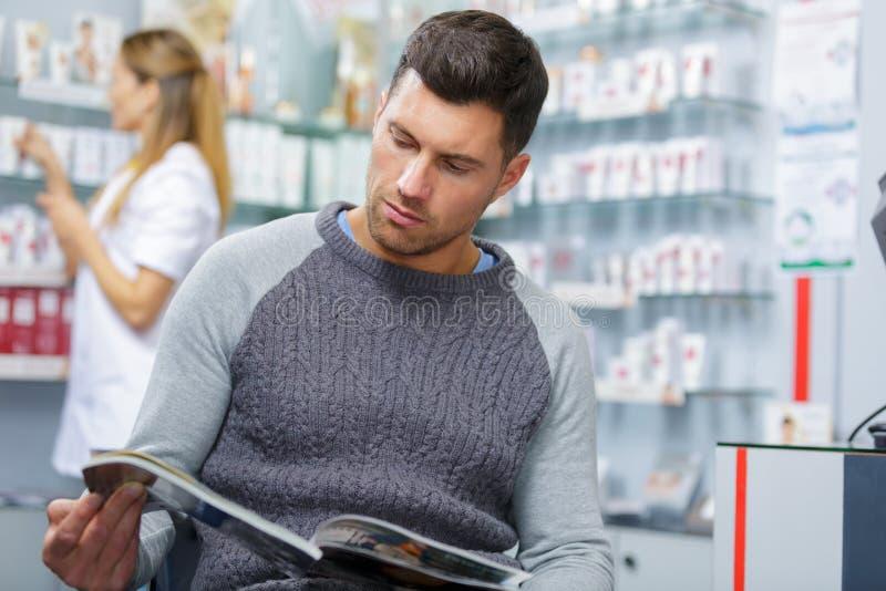 Libro di lettura dell'uomo in farmacia fotografia stock