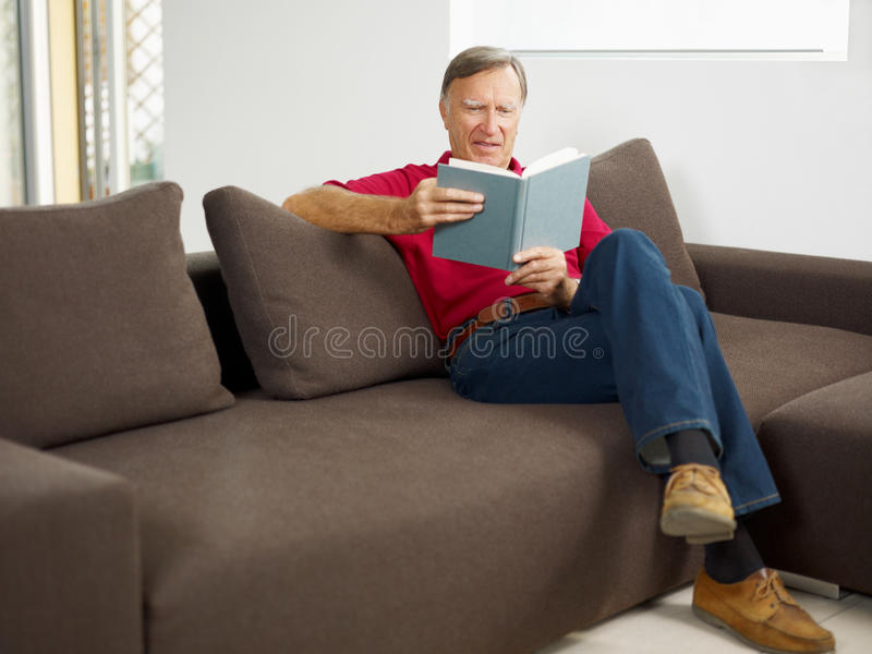 Libro di lettura dell'uomo maggiore fotografia stock