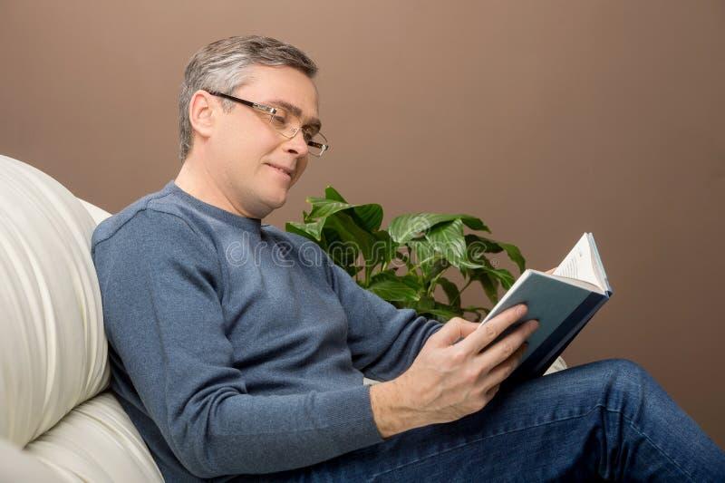 Libro di lettura dell'uomo più anziano sul sofà immagini stock libere da diritti