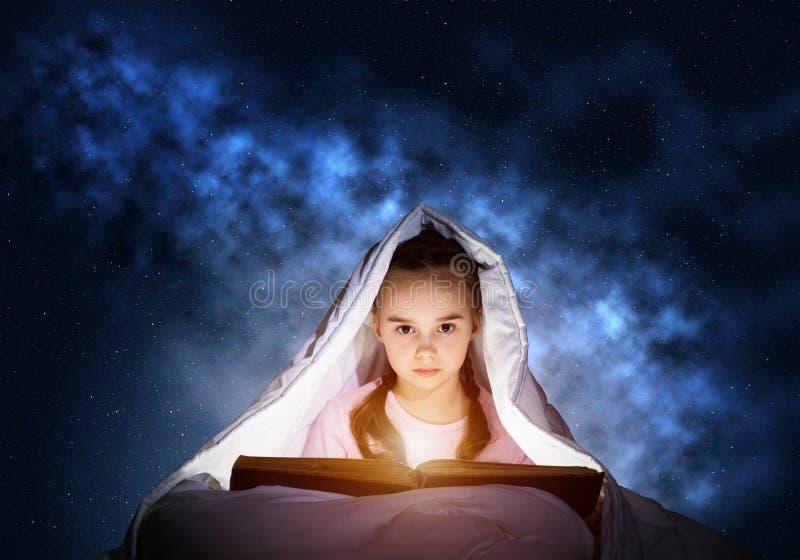 Libro di lettura della bambina a letto fotografie stock