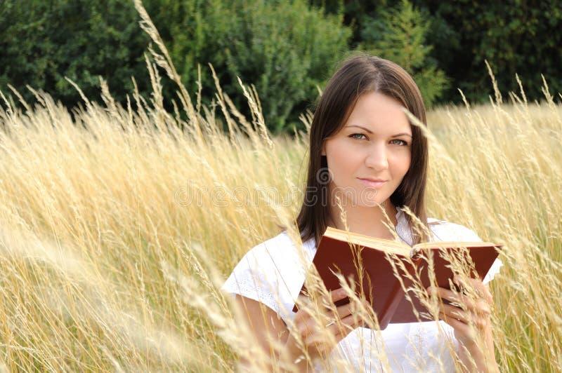Libro di lettura della donna nel campo fotografie stock libere da diritti