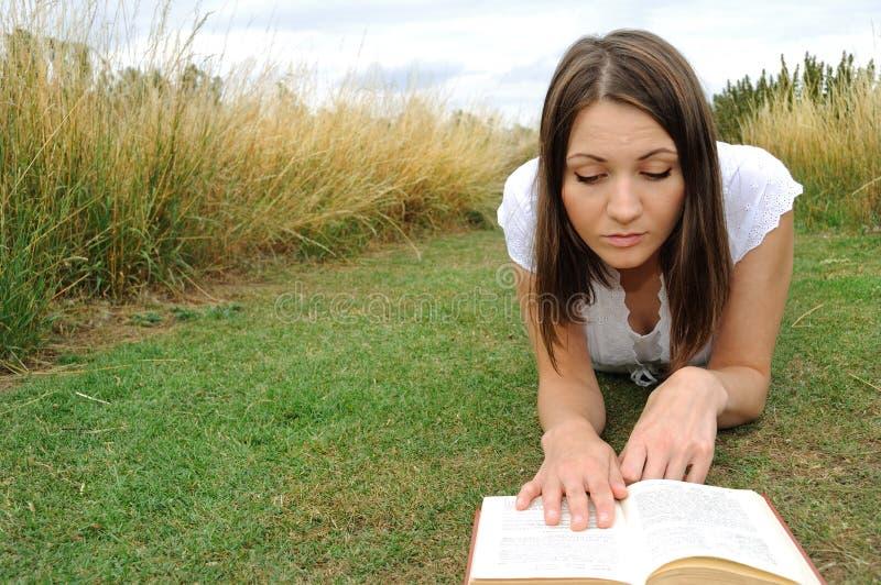 Libro di lettura della donna sul campo fotografia stock libera da diritti