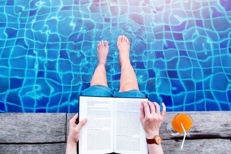 Libro di lettura della donna sul lato della piscina, rilassantesi con il riassunto immagine stock