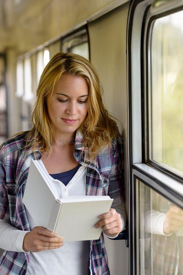 Libro di lettura della donna sulla vacanza del corridoio del treno fotografie stock libere da diritti