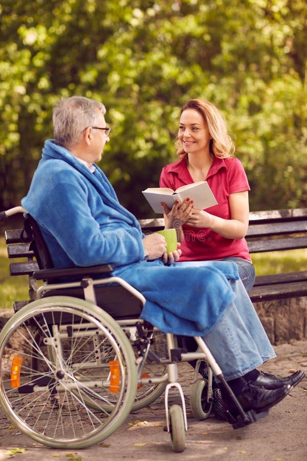 Libro di lettura della figlia all'aperto suo padre disabile in sedia a rotelle fotografia stock libera da diritti