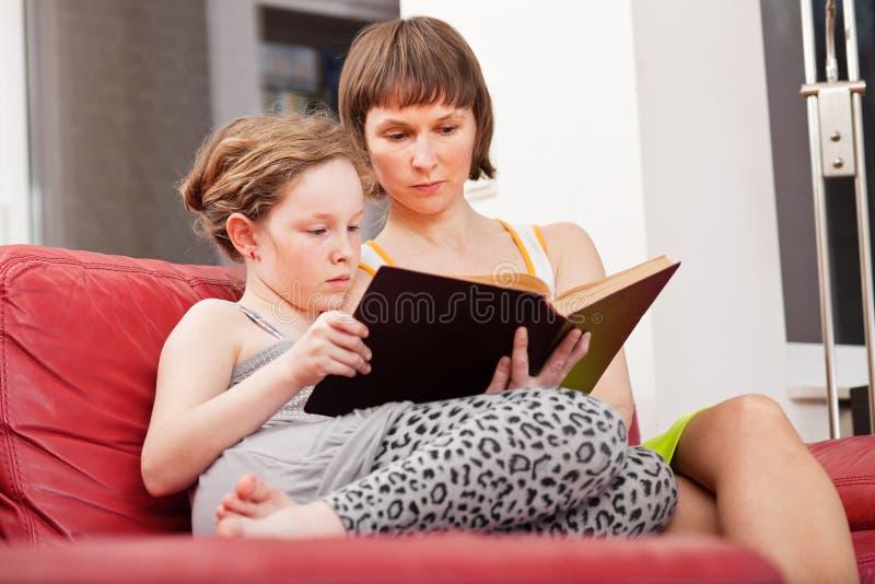 Libro di lettura della figlia e della madre insieme immagine stock
