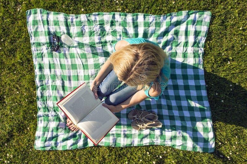 Libro di lettura della giovane donna in parco, visto da sopra fotografia stock