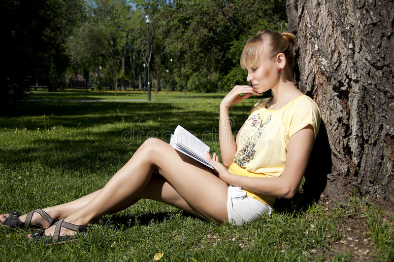 Libro di lettura della giovane donna in sosta fotografia stock libera da diritti