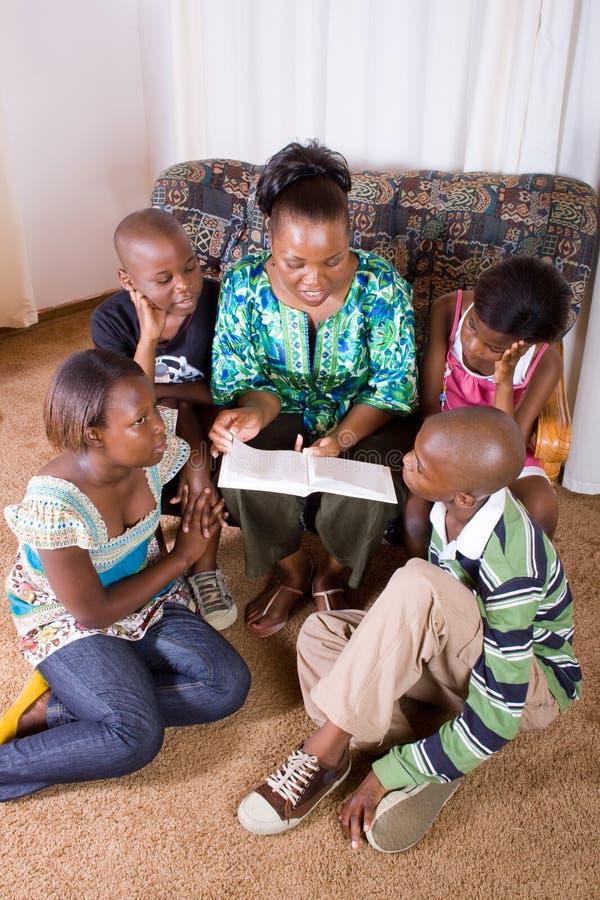 Libro di lettura della madre ai bambini fotografia stock