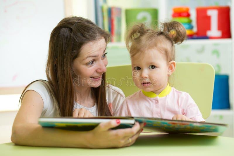 Libro di lettura della madre il suo bambino in scuola materna immagine stock