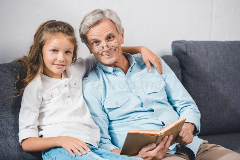 Libro di lettura della nipote e del nonno fotografie stock libere da diritti