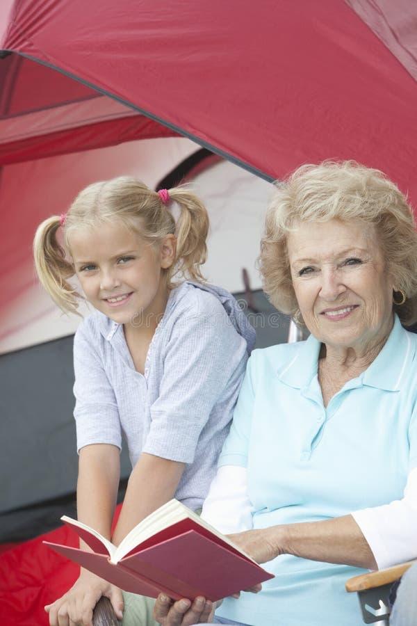 Libro di lettura della nonna con la nipote fuori di una tenda fotografie stock libere da diritti