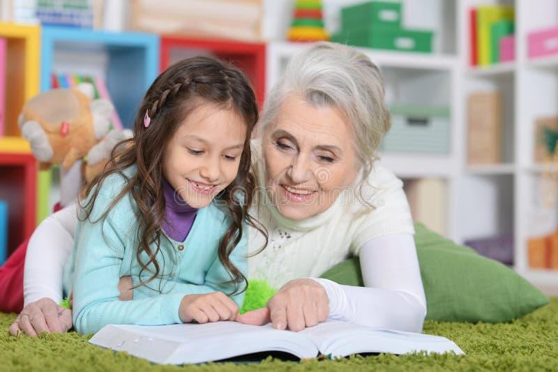 Libro di lettura della nonna con la sua nipote immagine stock