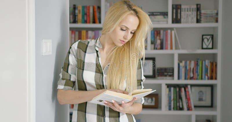 Libro di lettura della ragazza a casa immagine stock