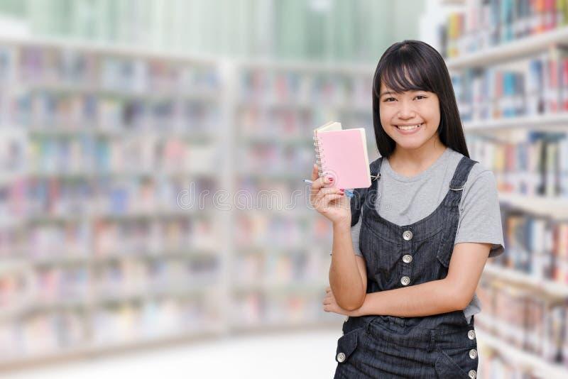 Libro di lettura della ragazza in libreria immagine stock libera da diritti