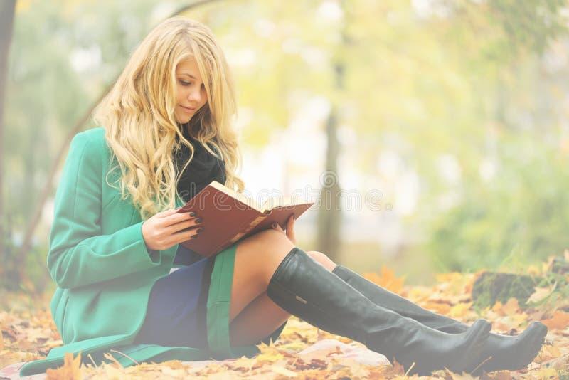 Libro di lettura della ragazza nella sosta di autunno fotografia stock
