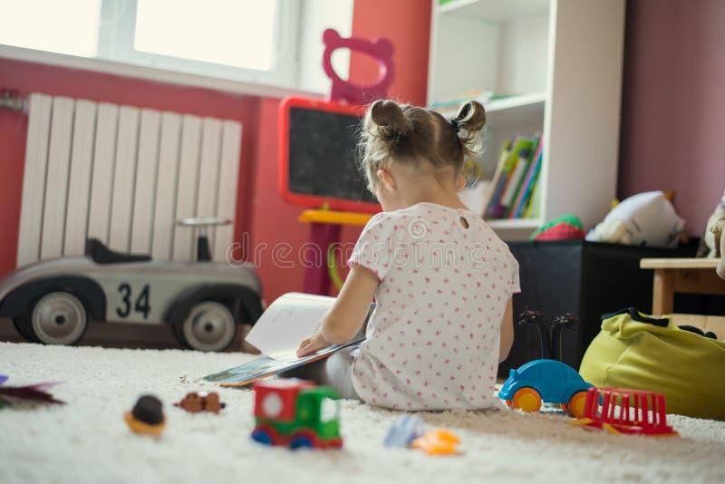 Libro di lettura della ragazza nella stanza di bambini fotografia stock libera da diritti