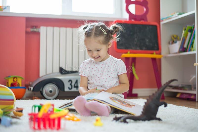 Libro di lettura della ragazza nella stanza di bambini fotografia stock