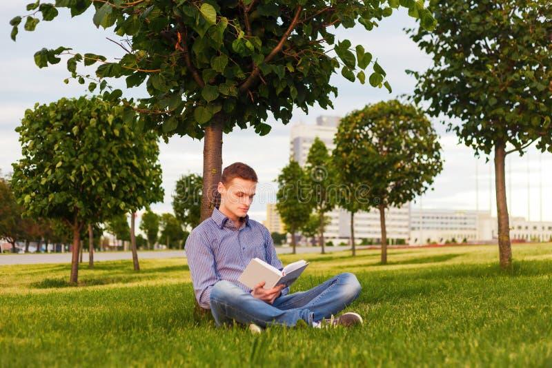 Libro di lettura dello studente che si siede nel parco sotto l'albero sull'erba immagini stock
