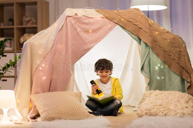 Libro di lettura felice del ragazzino in tenda dei bambini a casa fotografia stock libera da diritti