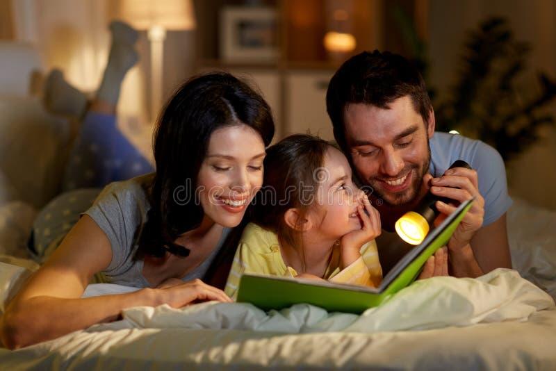 Libro di lettura felice della famiglia a letto alla notte a casa fotografie stock