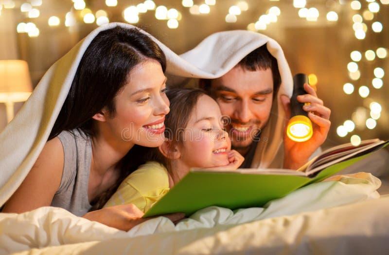Libro di lettura felice della famiglia a letto alla notte a casa immagine stock