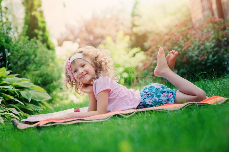 Libro di lettura felice della ragazza del bambino sulle vacanze estive nel giardino fotografia stock libera da diritti