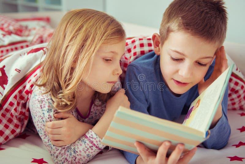 Libro di lettura felice di due bambini del fratello germano nel letto di cuccetta nell'ambito di blanke fotografia stock