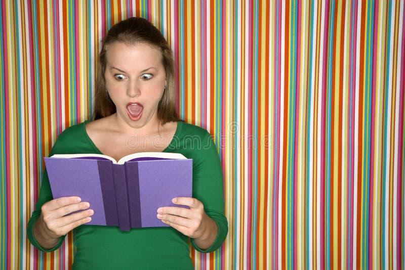 Libro di lettura femminile caucasico che fa espressione. fotografia stock