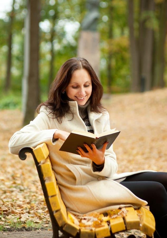 Libro di lettura grazioso della donna sul banco fotografia stock