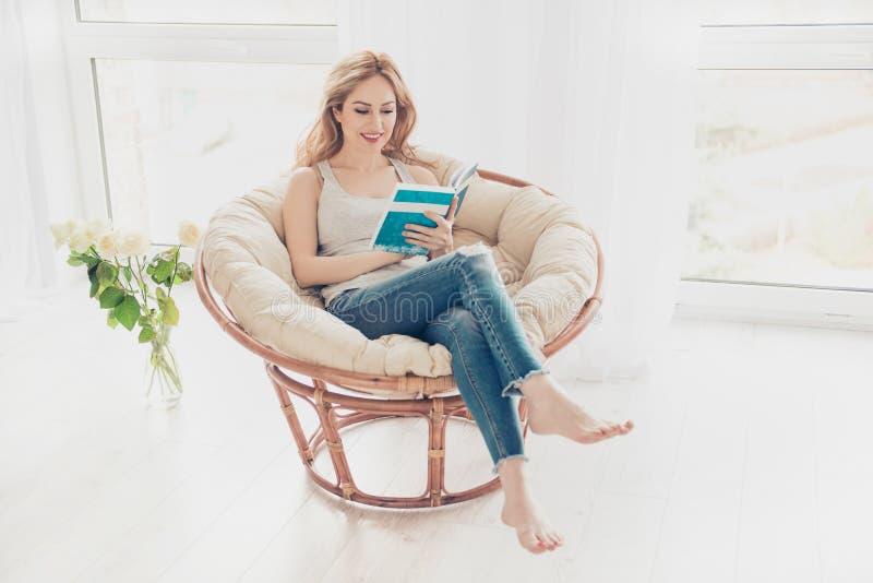 Libro di lettura grazioso sveglio felice della donna nella poltrona sulla settimana immagine stock