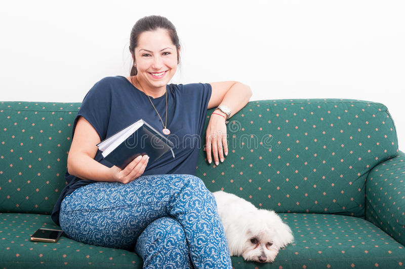 Libro di lettura rilassato della donna mentre sedendosi sullo strato immagine stock